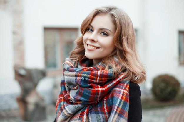 Ritratto di una ragazza carina con bellissimi occhi azzurri con un sorriso attraente con capelli biondi ricci in abiti invernali alla moda