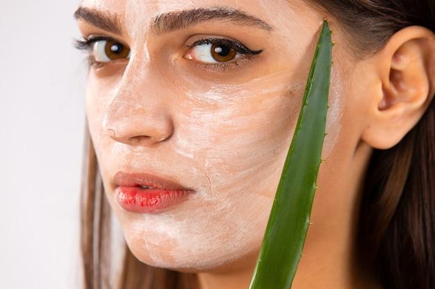 Ritratto di ragazza carina con una maschera facciale sul viso tenendo pezzi di aloe vera fresca. cura della pelle e trattamento, spa, bellezza naturale e concetto di cosmetologia. foto di alta qualità