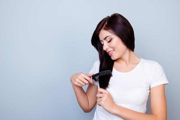 Ritratto di carino giovane donna sullo spazio grigio che pettina i capelli