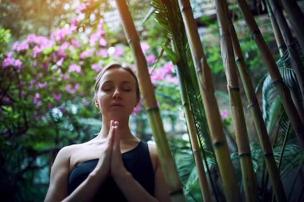 Ritratto di giovane donna sveglia che medita e che fa la mano del namaste in giungla.