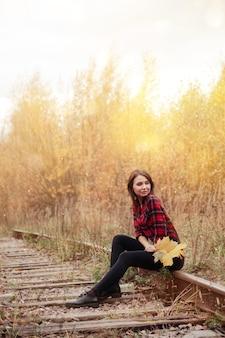 Ritratto di giovane donna carina di aspetto slavo in abbigliamento casual in autunno, su strada ferroviaria sullo sfondo di un parco e di un fiume autunnali. bella donna che cammina nella foresta in autunno dorato. copia spazio
