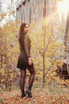 Ritratto di giovane donna carina di aspetto slavo in abiti scuri in autunno, in piedi sullo sfondo di un parco e di un fiume autunnali. bella donna che cammina nel parco in autunno dorato. copia spazio