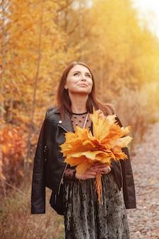 Ritratto di giovane donna carina di aspetto slavo con foglie in abbigliamento casual in autunno, in piedi sullo sfondo di un parco autunnale. bella donna che cammina nel parco in autunno dorato. copia spazio