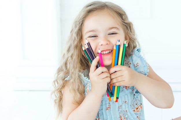 Ritratto delle matite della tenuta della bambina del cutew