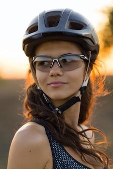 Ritratto di ragazza ciclista con casco da bici e occhiali