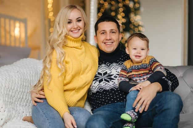 Ritratto di papà, mamma e figlio seduti su un pullman a casa vicino all'albero di natale, tutti sorridono. natale in famiglia. felicità.