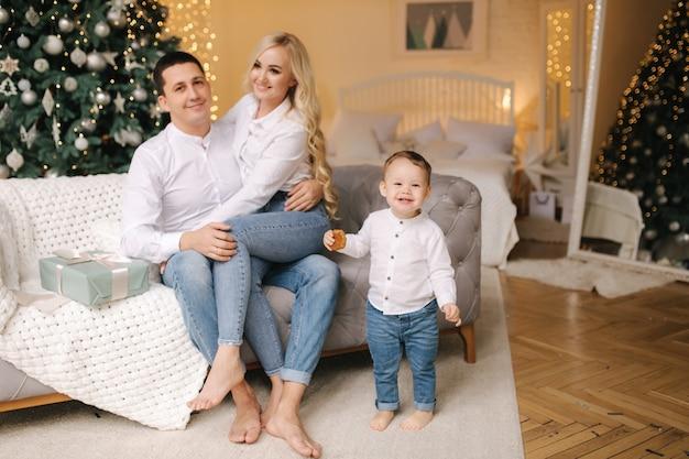 Ritratto di papà, mamma e figlio seduti per terra a casa vicino all'albero di natale, tutti sorridono. denim e camicie bianche. natale in famiglia. felicità.