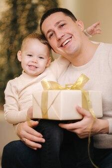 Ritratto di papà e figlio nel periodo natalizio. la famiglia felice ha trascorso del tempo insieme durante le vacanze. ragazzo