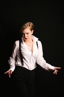 Ritratto di una ragazza che balla in una camicia bianca con bretelle e rossetto rosso.