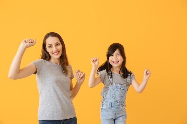 Ritratto di madre danzante con figlia sulla superficie del colore