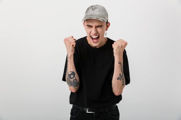 Ritratto di un uomo eccitato e felice che indossa abiti neri che urla e stringe i pugni su bianco