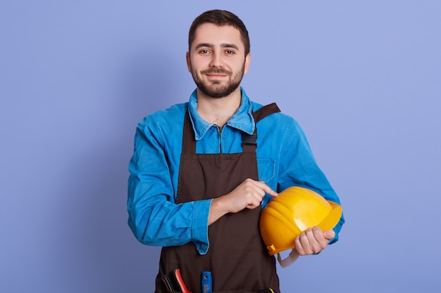 Ritratto del giovane felice di duro lavoro contentissimo, tenente casco giallo in una mano, indossando grembiule generale e marrone blu, posando isolato sopra la parete blu in studio.