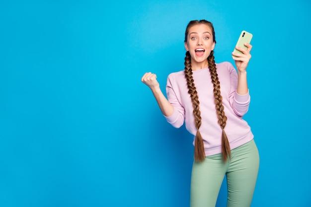 Ritratto di felice dolce giovane ragazza blogger utilizzare smartphone ottenere social network come notifica alzare i pugni urlare omg wow indossare pullover pantaloni verdi pantaloni isolati brillare colore sfondo