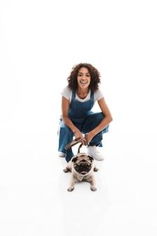 Ritratto di una donna felice vestita con una tuta di jeans accovacciata e posata con il suo cane carlino isolato su un muro bianco