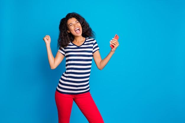 Ritratto di donna felice tenere il cellulare alza i pugni urlare sì