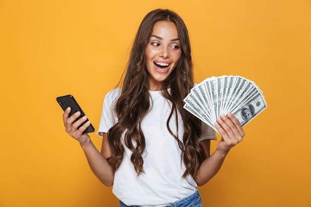 Ritratto di una giovane ragazza felice con lunghi capelli bruna in piedi sopra il muro giallo, tenendo le banconote in denaro, utilizzando il telefono cellulare
