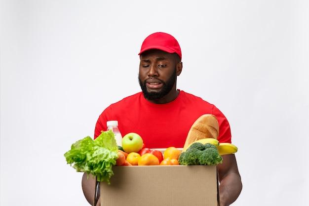 Ritratto dell'uomo afroamericano di consegna in camicia rossa. solleva scatole di generi alimentari pesanti