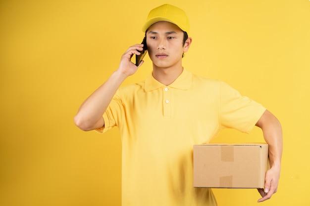 Ritratto del maschio di consegna che tiene il contenitore di carico e ascolta il telefono sulla parete gialla