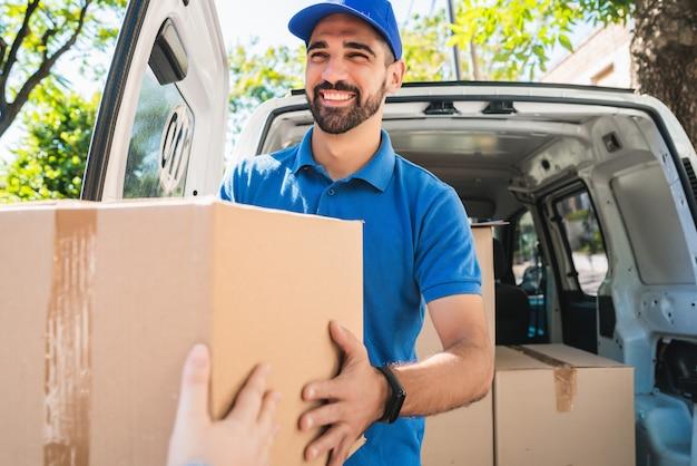 Ritratto di un uomo di consegna che trasporta i pacchi mentre effettua la consegna a domicilio al suo cliente. consegna e concetto di spedizione.
