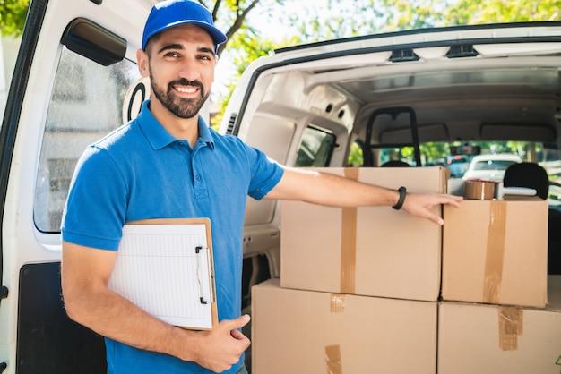 Ritratto di un uomo di consegna che controlla i prodotti nella lista di controllo mentre si trovava proprio accanto al suo furgone