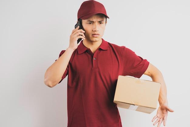 Ritratto di un uomo di consegna che tiene una scatola di carico e ascolta il telefono