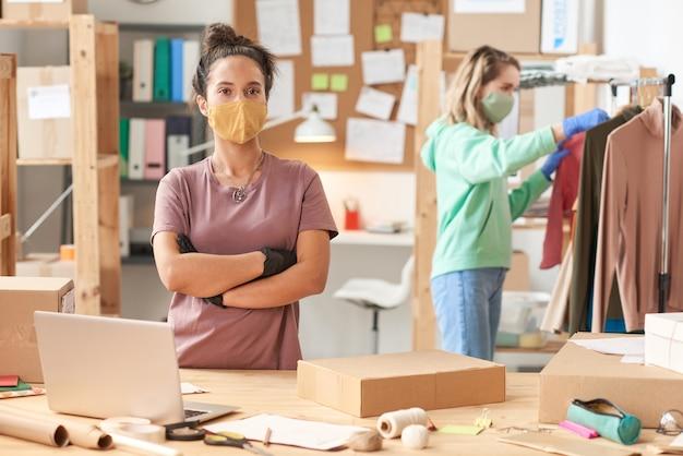 Ritratto di persona di consegna in maschera in piedi con le braccia incrociate guardando davanti durante il suo lavoro nel servizio di consegna