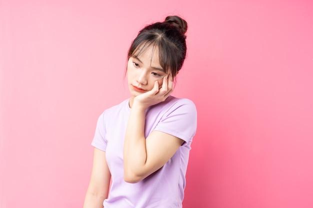 Ritratto di ragazza depressa, isolata sulla parete rosa