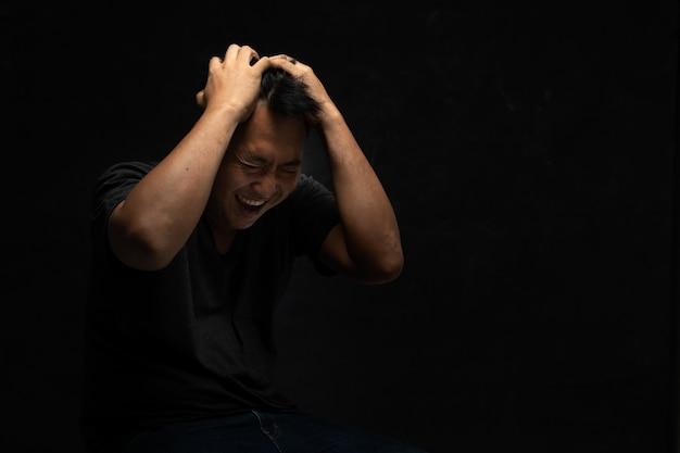Il ritratto dell'uomo triste depresso in difficoltà che si siede sulla sedia che tiene la testa in mani nel buio libera dallo spazio della copia. bancarotta, depressione, concetto emotivo solitario e negativo.