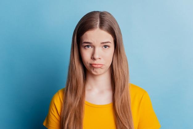 Ritratto di una ragazza adolescente depressa che guarda la telecamera sul muro blu