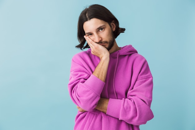 Ritratto di un giovane uomo brunetta barbuto depresso che indossa una felpa con cappuccio in piedi isolato su un muro blu