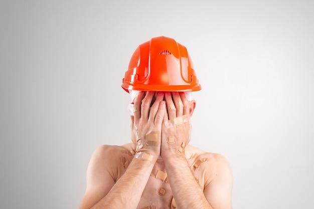 Ritratto di uomo disperato con la testa bendata con casco protettivo che copre il viso con le mani.