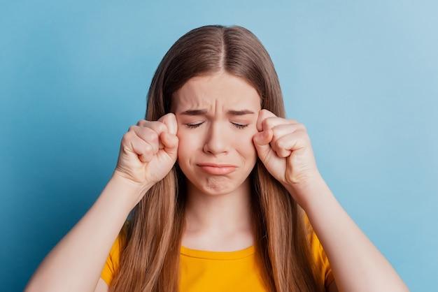 Ritratto di una ragazza disperata abusata e offesa che piange i pugni faccia su sfondo blu