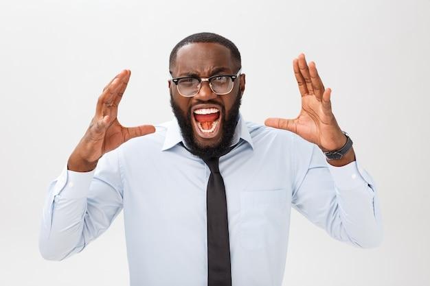 Ritratto di maschio nero infastidito disperato che grida di rabbia e rabbia strappandosi i capelli mentre si sente furioso e arrabbiato con qualcosa. n