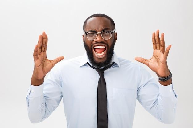 Ritratto di maschio nero infastidito disperato che grida di rabbia e rabbia strappandosi i capelli mentre si sente furioso e arrabbiato con qualcosa.