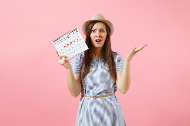 Ritratto di donna disperata in abito blu, cappello che tiene il calendario dei periodi per controllare i giorni delle mestruazioni isolati su sfondo rosa di tendenza brillante. concetto medico, sanitario, ginecologico. copia spazio