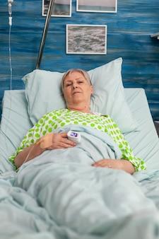 Ritratto della donna anziana del pensionato di invalidità che si trova nel letto di ospedale che esamina macchina fotografica