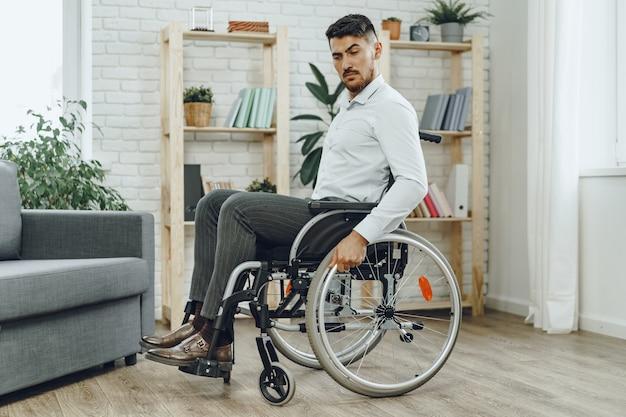 Ritratto di uomo disabile in abbigliamento formale seduto su una sedia a rotelle al chiuso