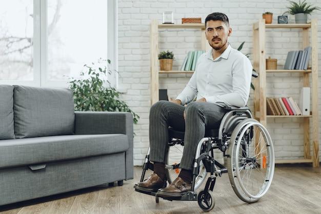 Ritratto di uomo disabile in abbigliamento formale seduto su una sedia a rotelle