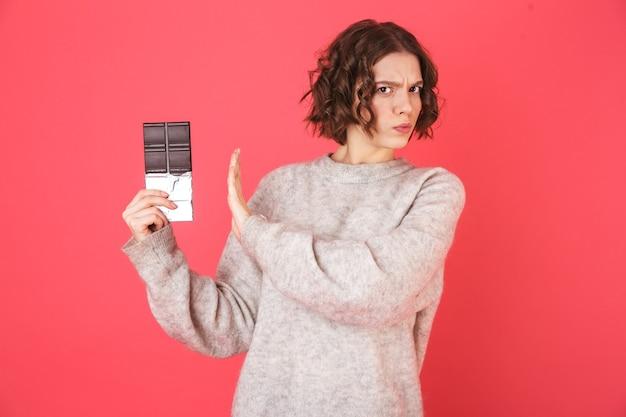 Ritratto di una giovane donna delusa in piedi isolato su rosa, mostrando il piatto di cioccolato