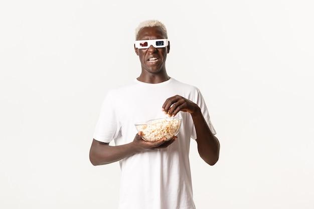 Ritratto di ragazzo biondo afroamericano disgustato guardando qualcosa di spiacevole, rabbrividire dal film, indossando occhiali 3d e mangiando popcorn