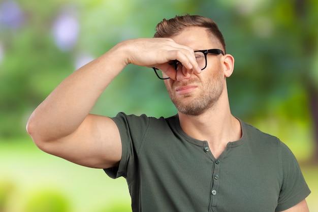 Ritratto di uomo disgustato pizzica il naso con le mani delle dita guarda con disgusto qualcosa puzza di cattivo odore