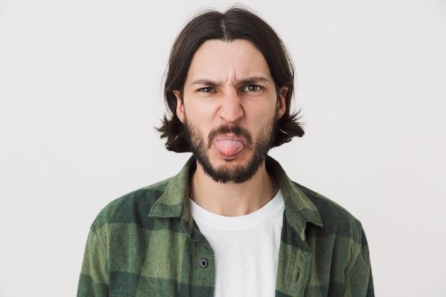 Ritratto di un giovane uomo brunetta barbuto disgustato che indossa una camicia a quadri in piedi isolato su un muro bianco