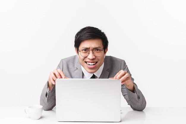Ritratto di uomo d'affari asiatico scontento, scettico e giudizioso in auricolari wireless, scrivania, indicando lo schermo del laptop con espressione delusa sconvolta, su un muro bianco