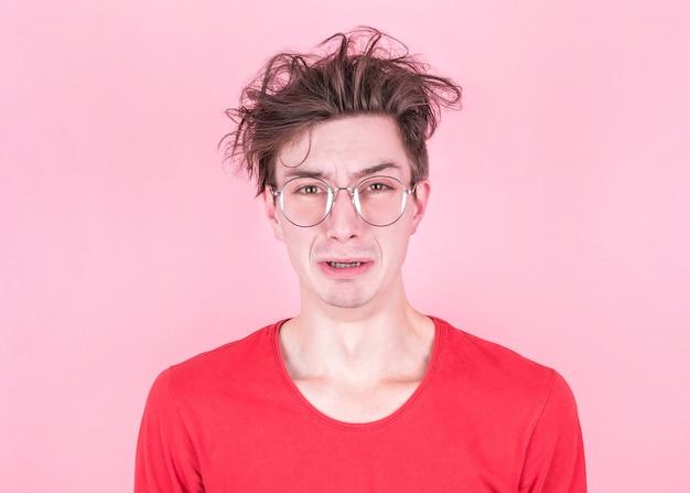 Ritratto di orinato arrabbiato maschio aggrotta le sopracciglia faccia come andare a piangere, isolato su sfondo rosa studio.