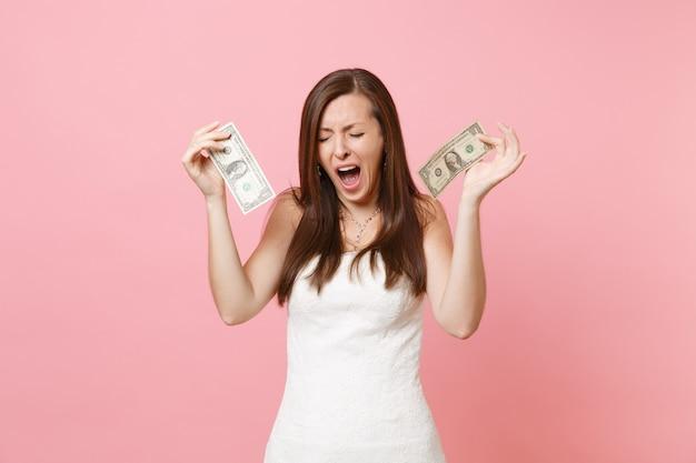 Ritratto di donna insoddisfatta in abito bianco che piange tenendo in mano banconote da un dollaro