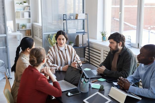 Ritratto di un gruppo eterogeneo di uomini d'affari al tavolo che collaborano durante la riunione informativa in ufficio, concentrarsi sul manager femminile mediorientale