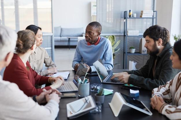 Ritratto di diversi gruppi di uomini d'affari al tavolo che collaborano durante la riunione informativa in ufficio, concentrarsi sull'uomo afroamericano sorridente
