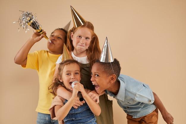 Ritratto di gruppo eterogeneo di bambini che indossano cappelli da festa urlando al microfono mentre posa sul beige