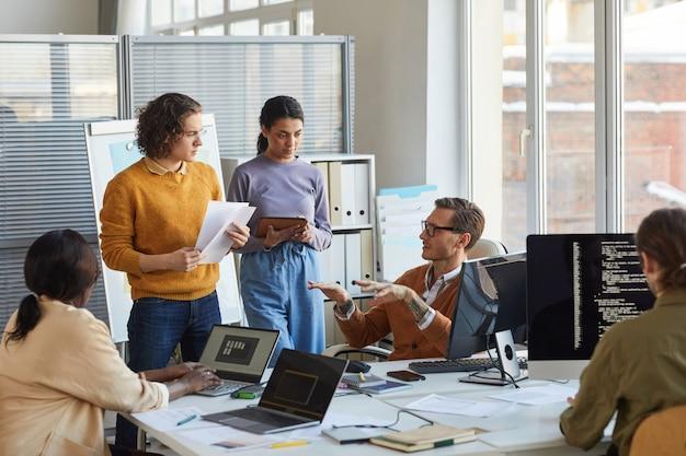 Ritratto di diversi team di sviluppo software che collaborano al progetto in un ufficio moderno, concentrarsi sull'ingegnere capo che istruisce i colleghi, copia spazio