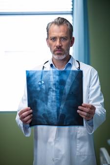 Ritratto di medico che analizza raggi x pazienti in reparto